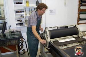 De clichéplaten worden onder de pers door gehaald; de druk wordt tot op de tiende millimeter ingesteld.